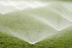 Irrigating of grass with water sprinkler stock photography