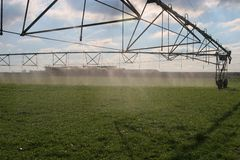 Irrigation 3. Large center pivot irrigation system running on an open plains dairy farm in Canterbury, New Zealand.  Water droplets all over the place, Sheep Royalty Free Stock Photo