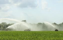 Irrigation. Vehicles irrigating in open field stock photos