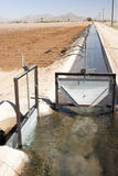 Irrigation canal. An irrigation canal with gates and siphon tubes beside a field in Arizona Royalty Free Stock Images