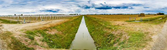 irrigation canal divides harvested land  and plowed land with pr Stock Photos