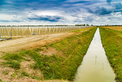 irrigation canal divides harvested land  and plowed land with pr Stock Photography