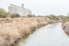 Irrigation canal and grain silos Royalty Free Stock Photos
