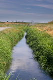 Irrigation canal provides water to crops Stock Photos