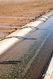 Irrigation canal & siphon tubes. An irrigation canal and siphon tubes beside a field in Arizona Stock Photos