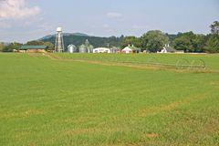 Irrigation Line. An irrigation line in a green fallow field, farm buildings in the background Royalty Free Stock Photography