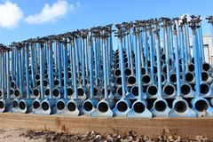 Irrigation pipes, blue color, stacked on each other for storage. Against a blue sky background royalty free stock photography