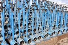 Irrigation pipes, blue colored, stacked on each other, blue sky. Background stock photos