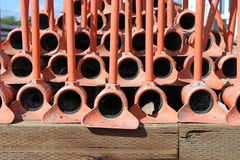 Irrigation pipes, red, stacked on each other for storage. Against a blue sky background stock image