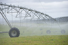 Irrigation by Pivot sprinkler on grass field Royalty Free Stock Photography