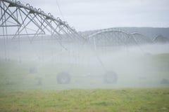 Irrigation by Pivot sprinkler spray on grass field Royalty Free Stock Photography