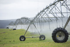 Irrigation by Pivot sprinkler system on grass field Stock Image
