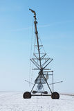 Irrigation pivot in winter. Image of an irrigation pivot in a field covered by snow in winter Stock Image