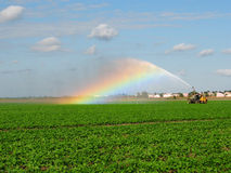 Irrigation Pump. An Irrigation truck sprays water over beans field creating a rainbow in the process Royalty Free Stock Image