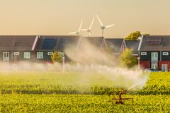 Irrigation sprinkler on farmland in front of Dutch houses royalty free stock photo