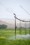 Irrigation sprinkler system. Irrigation - automated linear sprinkler system  in operation Stock Photos