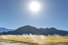 Irrigation sprinklers water a dry field by mountains Royalty Free Stock Images