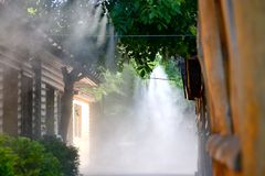 Irrigation system close-up. Humidification of air by steam on the street outdoor in a hot summer day morning Royalty Free Stock Photo