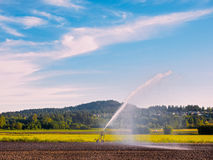 Irrigation system watering freshly seeded field Royalty Free Stock Image
