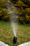 Irrigation system. Watering grass with a modern irrigation system Royalty Free Stock Photo