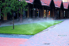 Irrigation system watering the lawn. Sprinkler system watering the lawn watering green lawn Royalty Free Stock Photo