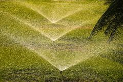 Irrigation watering system with sprinkler heads watering green grass royalty free stock image