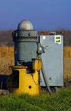 Irrigation Well Head. Well pump head for irrigating crops with blue sky and grass Stock Image