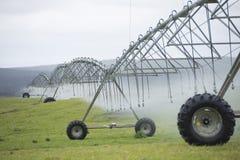 Irrigazione dal sistema antincendio del perno sul campo di erba Immagine Stock