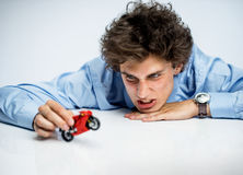 Irritable office worker plays with toy motorbike. / photos of immature man wearing blue shirt over gray background Stock Images