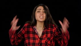 Irritable woman outraged then grabs her head and screams. Black. Close up. Irritable woman shouts, outraged and something to prove. Female in a plaid red shirt stock video