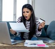 Irritado fêmea novo forçado infeliz com finança home calculadora da conta de cartão de crédito e contas pagando imagem de stock royalty free