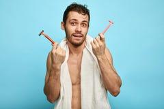 Irritated озадачило человека идя побрить бороду, держит острые 2 бритвы стоковое фото