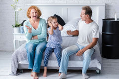 Irritated aged couple quarreling in front of their granddaughter Royalty Free Stock Photos