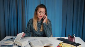 Irritated and angry female student in a denim shirt, talking on a smartphone. the moment when she does the homework. She stock video