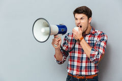Irritated angry young man in plaid shirt shouting with loudspeaker Stock Photos