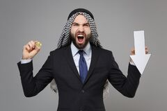 Irritated arabian muslim businessman in keffiyeh kafiya ring igal agal black suit isolated on gray background