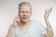 Annoyed male with frowned face recieving unpleasant news on mobile phone. stock images