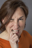 Irritated beautiful middle aged woman biting her finger, winking Royalty Free Stock Photography
