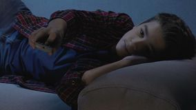 Irritated boy changing tv channels trying to find film at night, adult content stock video