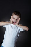 Irritated Boy Shouts at Camera with Hands on Face. Half Body Shot of an Irritated Young Boy in White Casual Shirt, Shouting at Camera with Hands on his Face Stock Image