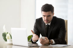 Irritated businessman annoyed with phone call, bad message, brok. Angry businessman annoyed with phone call while working on laptop at office, receiving bad news Royalty Free Stock Image