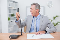 Irritated businessman answering phone Royalty Free Stock Photos