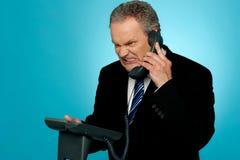 Irritated businessman communicating on phone Stock Image