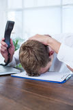 Irritated businessman holding a land line phone. In the office Royalty Free Stock Images