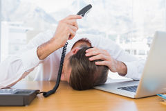 Irritated businessman holding the phone Royalty Free Stock Photos