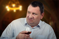 Irritated businessman holds glass of brandy Royalty Free Stock Photos