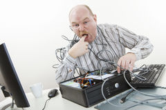 Irritated Businessman Licking Finger While Repairing Computer Royalty Free Stock Photography