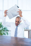 Irritated businessman about to break his laptop Royalty Free Stock Photo