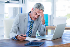 Irritated businessman trying to work Royalty Free Stock Images
