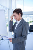 Irritated businesswoman looking at clipboard Royalty Free Stock Photography